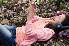 Sourire rose de téléphone d'écouteurs de primevères de fille Photos stock