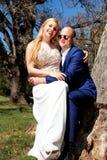 Sourire se reposant de couples heureux à l'arbre Photographie stock libre de droits