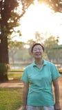 Sourire supérieur asiatique de femme en soleil avec le backgro de nature de matin Photo libre de droits
