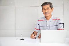 Sourire sup?rieur d'homme d'affaires de l'Asie et signer dedans le document de contrat photographie stock libre de droits
