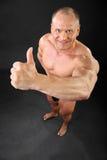 Sourires déshabillés et pouces de bodybuilder vers le haut Photographie stock libre de droits