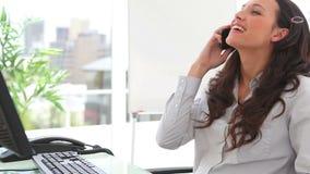 Sourires de femme d'affaires comme elle répond à un téléphone Image libre de droits