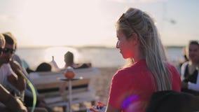 Sourires et regards femelles blonds mûrs attrayants à la caméra se reposant à la plage banque de vidéos