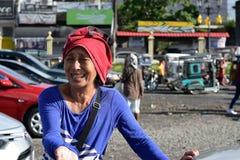 Sourires mûrs ethniques de femme comme elle prie pour l'aumône à la vieille cour d'église Fin vers le haut image libre de droits