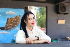 Sourires merveilleux de jeune femme, regards à l'appareil-photo et à la pose, sittin Photographie stock libre de droits