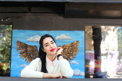 Sourires merveilleux de jeune femme, regards à l'appareil-photo et à la pose, sittin Photo stock