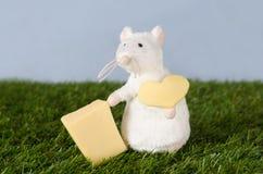 Souris avec du fromage sur l'herbe Image stock