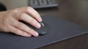 Souris d'ordinateur dans une main du ` s de femme banque de vidéos