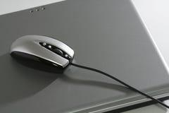 Souris sur un ordinateur portatif argenté Photographie stock libre de droits