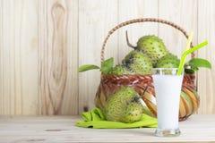 Soursopfruktsaft med soursopfrukt i korg på trätabellen arkivbild