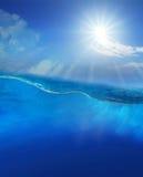 Sous l'eau bleue avec le soleil brillant en haut Photos libres de droits
