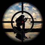 Sous la menace des armes silhouette de terroriste contre le coucher du soleil Photographie stock libre de droits