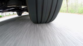 Sous la vue de voiture du pneu sur une rue suburbaine banque de vidéos