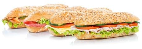 Sous sandwichs à baguette avec les poissons saumonés de fromage de jambon de salami entiers photos stock