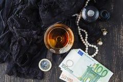 Sous-vêtements, cognac et argent pour symboliser le coût du sexe Photographie stock