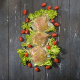 Sous Vide cooking concept. Vacuum packed ingredients arranged on wooden dyed background. Top View stock photography