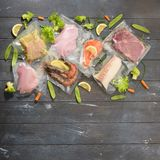 Sous Vide cooking concept. Vacuum packed ingredients arranged on wooden dyed background. Top View stock photos