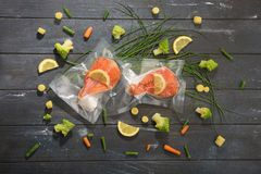 Sous Vide cooking concept. Vacuum packed ingredients arranged on wooden dyed background. Top View stock image