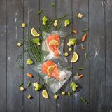 Sous Vide cooking concept. Vacuum packed ingredients arranged on wooden dyed background. Top View stock images