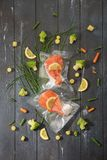 Sous Vide cooking concept. Vacuum packed ingredients arranged on wooden dyed background. royalty free stock image