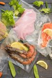 Sous Vide cooking concept. Vacuum packed ingredients arranged on wooden dyed background. stock images
