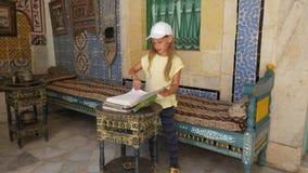 Sousse, Tunesien - 15. Juni 2018: Mädchen, das altes Buch im historischen Kunst- und Kulturmuseum im Palast in Medina schaut stock video