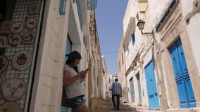 Sousse, Tunisia - June 15, 2018. Traveling woman using mobile phone at narrow street in old city stock video