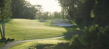 Soutenez le fairway allumé de golf vu de la boîte de pièce en t Photos stock