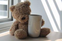 Soutenez le jouet avec la tasse se reposant par la fenêtre dans les ombres Photographie stock libre de droits