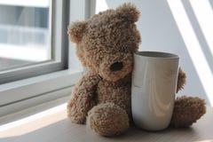 Soutenez le jouet avec la tasse se reposant par la fenêtre dans les ombres Images stock