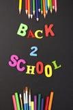 Soutenez 2 lettres et papeterie colorées d'école sur le fond de tableau noir avec le copyspace pour votre texte Concept pour le v Images stock