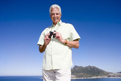 South Africa, Cape Town, mature man holding binoculars by sea, smiling, portrait, low angle view Photo stock