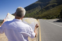 South Africa, Cape Town, mature man looking at map by road, rear view Royalty Free Stock Photography