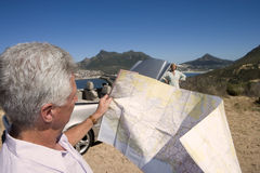 South Africa, Cape Town, mature man looking at map, woman by car in background Stock Photos