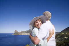 South Africa, Cape Town, senior couple embracing by sea, smiling, portrait of woman Stock Image