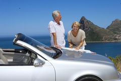 South Africa, Cape Town, senior couple standing by car with map, smiling, sea in background Royalty Free Stock Photos
