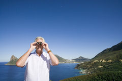 South Africa, Cape Town, senior man looking through binoculars by sea Royalty Free Stock Photo