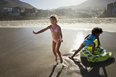 South Africa, Cape Town, two girls (6-10) playing with inflatable toy on sandy beach, smiling Royalty Free Stock Images