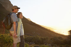 South Africa, couple admiring view from hilltop at sunset, smiling, side view, sea in background Stock Photography