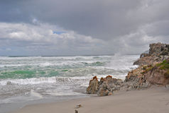 South Africa, Garden Route, beach, waves, fynbos. South Africa, 21/09/2009: stormy Ocean and weather on the beach of Hermanus, a town on the southern coast of Stock Photos