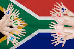 South Africa inscription on the children`s hands against the background of a waving flag of the South Africa royalty free stock photo