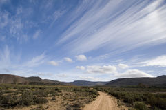 South Africa Landscape with sweeping clouds. South Africa Landscape with spectacular sweeping clouds. Red rugged outback road across low bush land stock photography
