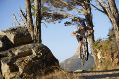 South Africa, male mountain biker in mid-air over dirt track, front view Stock Photos
