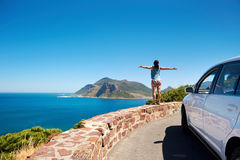 South africa tourist. Carefree tourist stands on chapmans peak drive with arms outstretched in freedom girl pose with rental car Stock Photos