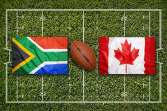 South Africa vs. Canada flags on rugby field. South Africa vs. Canada flags on green rugby field Stock Image