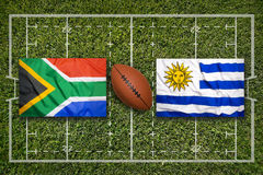 South Africa vs. Uruguay flags on rugby field Stock Photos