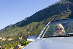 South Africa, Western Cape, senior woman driving silver convertible car along mountain road, smiling, front view, portrait (tilt) Stock Photography