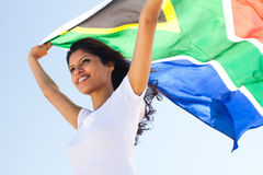 South african. Young happy south african woman holding a south africa flag outdoors stock image