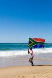 South african. African man running on beach with a south african flag, new south africa 2010 world cup concept Royalty Free Stock Images