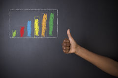 South African or African American teacher or student thumbs up against blackboard chalk bar graph Royalty Free Stock Photos